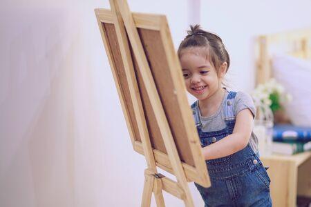 Litte girl draws a chalk on a blackboard