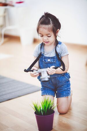 Little girl holding camera and taking macro at home