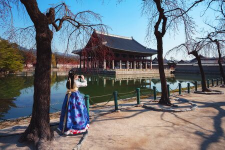 Female traveler in korean national dress or Hanbok traveling into the Gyeongbokgung Palace with cherry blossom, Seoul South Korea