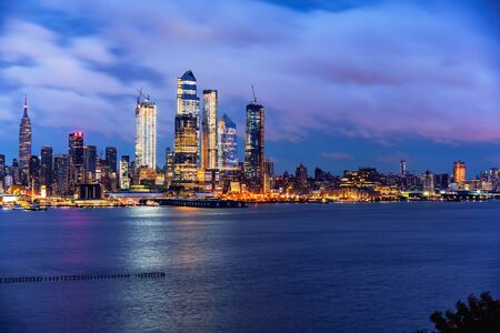 New York City Manhattan skyline panorama at night over Hudson River with refelctions viewed from New Jersey Standard-Bild - 130177297