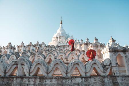 Novices under umbrellas at historic temple, Mingun, Mandalay, Myanmar Stockfoto
