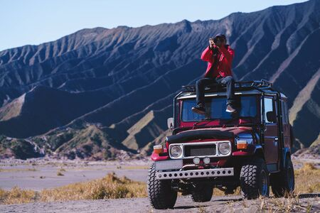 Male tourists stay 4x4 Car service for sight seeing around Bromo mountain tour, Indonesia Standard-Bild - 135297381