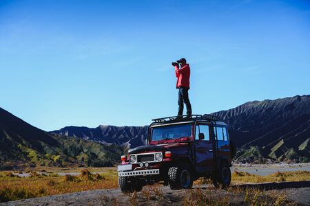 Male tourists stay 4x4 Car service for sight seeing around Bromo mountain tour, Indonesia Standard-Bild - 135297382
