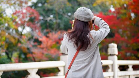 Female tourists stand in the bridge, Looking at autumn leaves, Kyoto Japan. Standard-Bild - 136080738