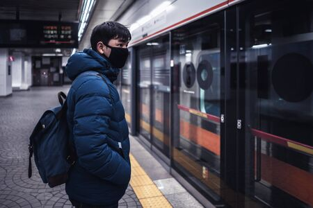 Asian male traveller cover mouth and cough, wear medical face mask to protect from infection of viruses, pandemic, outbreak and epidemic of disease in crowded underground train, Seoul South Korea Standard-Bild - 144204494