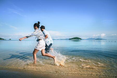 Asian teenage girl and boy running on the beach, Koh Mak Thailand
