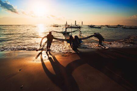 Silhouette of fishermen with Traditional fishing boats Bali, Indonesia Standard-Bild