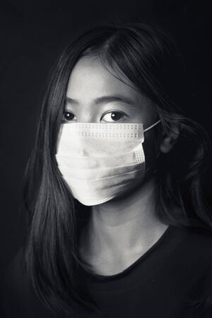 Asian young girl wearing medical face mask, studio portrait