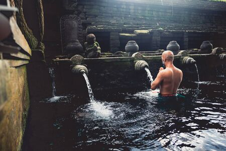 Man at the holy spring water is praying at Pura Tirta Empul temple during a religious ceremony Standard-Bild