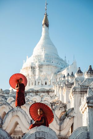 Novices under umbrellas at historic temple, Mingun, Mandalay, Myanmar Standard-Bild - 148404840