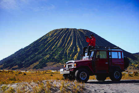 Male tourists stay 4x4 Car service for sight seeing around Bromo mountain tour, Indonesia Фото со стока