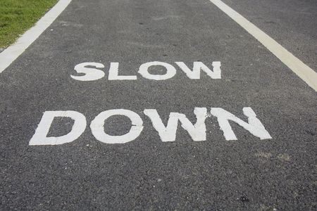 slow lane: Worded marking SLOW DOWN painted on the bike lane to warn bikers to slow down