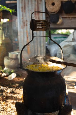 Boiling golden cocoon of silkworm in the pot to process to silk thread