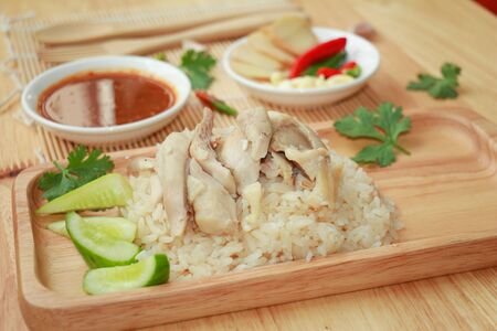 Hainanese chicken rice, Thai gourmet steamed chicken with rice or khao man kai and ingredients with seasoning on wooden plate Stock Photo