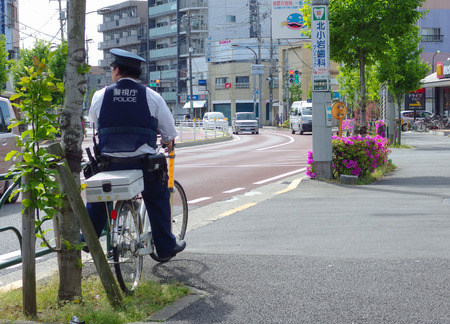 2017 April 05. TOKYO JAPAN. A policeman on bicycle looking for the safty of population in EDOKAWA city.