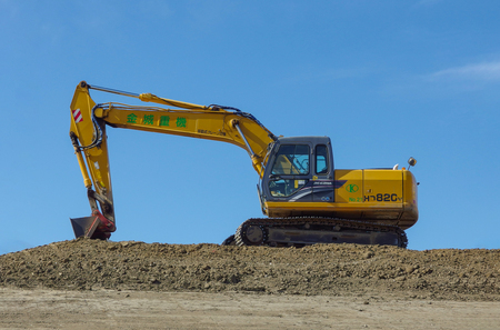 2017 Februar 19. Tokio Japan. Japanischer gelber Kato Regzam HD820V Baggerwagen steht zum Graben des Bodens der Baustelle bereit.