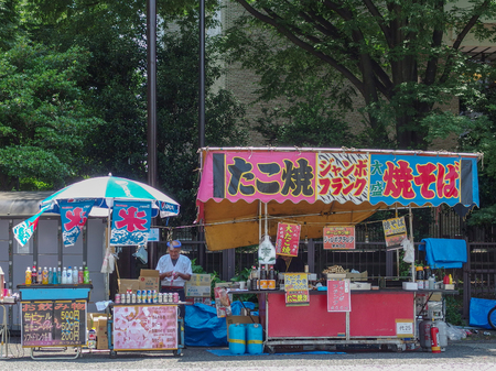 2016 June 18. Tokyo JAPAN. an old japanese man prepare traditional food and drink outdoor shop or yatai on festival.