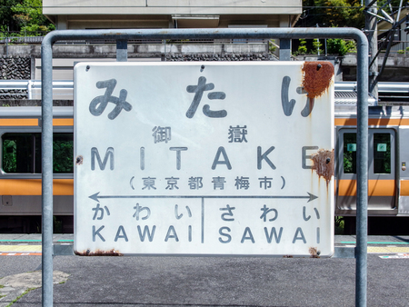 2016 May 05. TOKYO JAPAN. An old white rusty metal information board which had Japanese kanji letter word as MITAKE Station.
