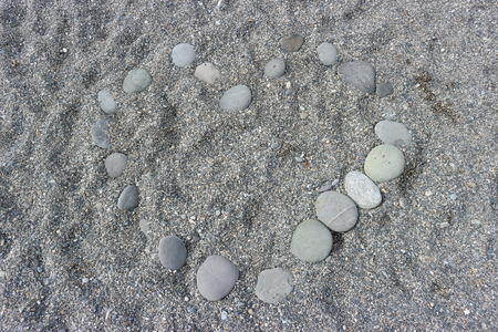 sorted stone in heart shape on the sand.