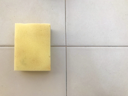 yellow sponge for wash cleaning on ceramic tile wall background.