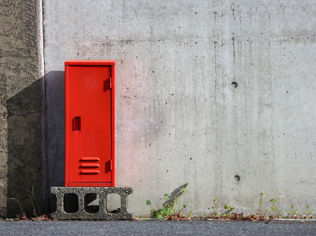Japanese red fire extinguisher keep box with cement wall as background. 免版税图像