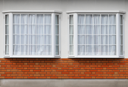 modern glass window with brick block on cement facade wall background.