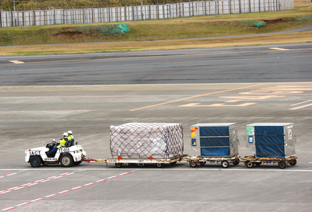 2018 December 14. Narita airport Japan. A baggage transfering car running on the parking place to moving baggage into next flight.