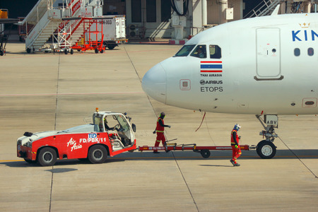 2018 December 14. Bangkok Thailand. airport ground worker moving an Air Asia airline plane to prepare for take off at donmueng international airport.