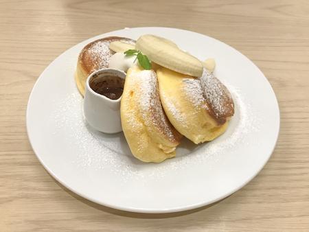 Yummy hot fresh pancakes with syrub dish on wood table background.