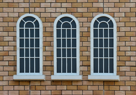 classical vintage design window on weathered red brick blocks wall background.
