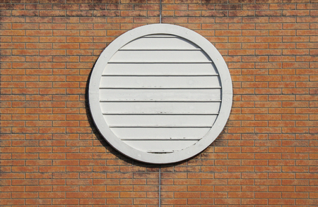 retro style circle design window on aged brick block wall background.