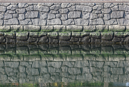 a natural stone wall with reflection on water surface near river side.
