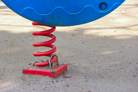 a red spring part the child fun play park toy located strongly with sand ground. Standard-Bild