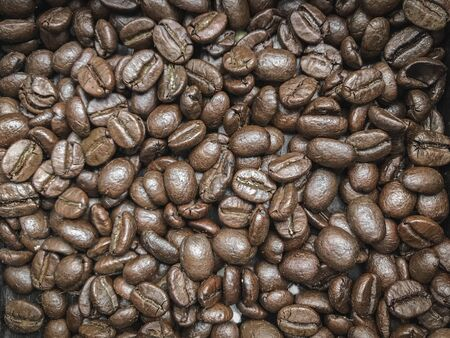 Roasted fresh coffee beans stack background.