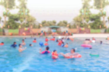 Blurred Crowd people playing in swimming pool on summer day background.