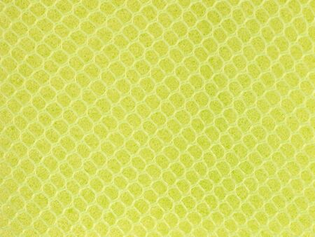 Yellow wire mesh on sponge surface background. Archivio Fotografico