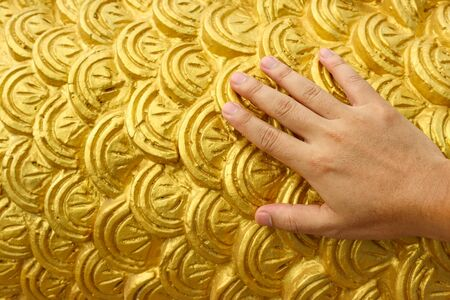 Humand hand touching golden cement plaster in fish skin curve pattern wall background. Stockfoto