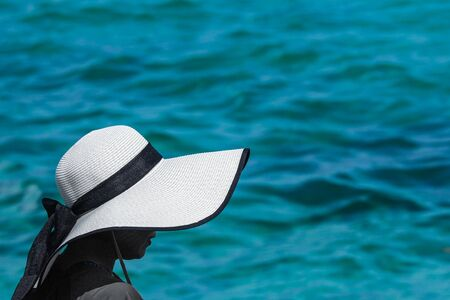 back of a woman who wearing a craft hat with the sea as backgorund.