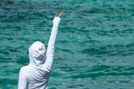 A white cloth girl who making a victory sign hand with the sea as background. Stok Fotoğraf