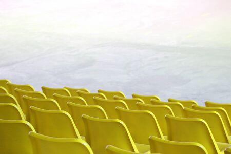 Des sièges jaunes en plastique vides s'alignent au spectacle intérieur du stade ou à l'arrière-plan du terrain de sport. Banque d'images