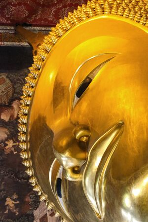 Face part of Big Golden reclining Buddha statue at Wat pho Thailand.
