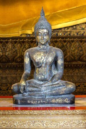 an ancient Black sitting Buddha statue in Wat Pho church. Standard-Bild