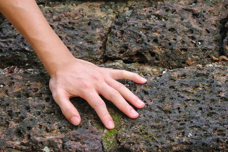 Human hand touch on old weathered laterite wall background.