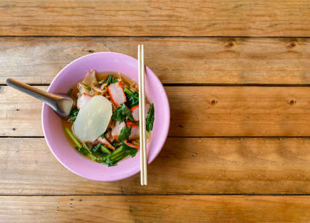 top view of Thai yellow noodle bowl on wood table background.