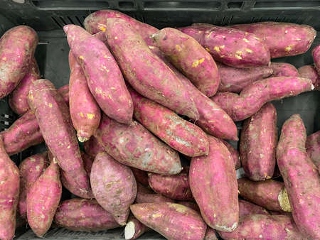 Raw Japanese red potatoes stack for sale in market.