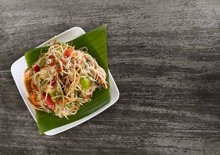 Thai Food healthy SOM TUM dish on old dark wood table background.