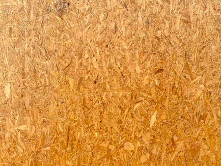 Top view of OSB brown wood chips veneer texture surface wall background.