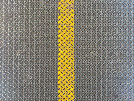 yellow line on old weathered metal plate surface texture wall background.