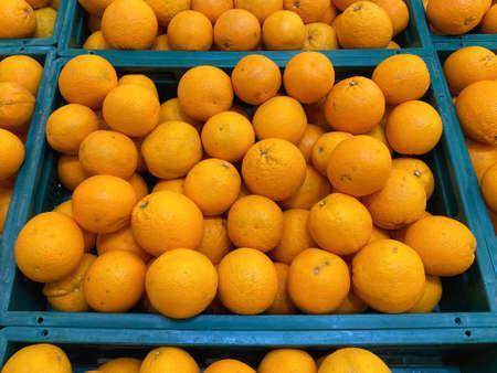 stacks of fresh orange on the basket for sale at supermarket store.