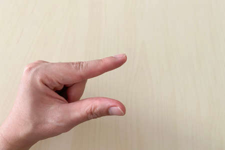 human hand making body language sign as a little bit or small meaning.